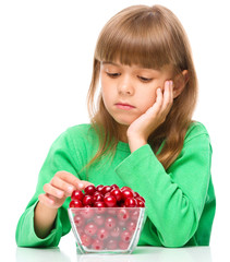Cute girl doesn't want to eat cherries
