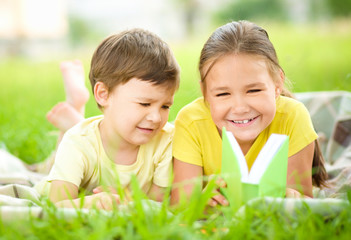 Little girl and boy are reading book outdoors
