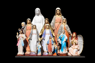 Many statues of the Virgin Mary on a black background.