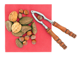Nuts with nutcracker on red napkin, isolated on white. Festive s