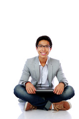 Smiling asian man sitting on the floor with laptop
