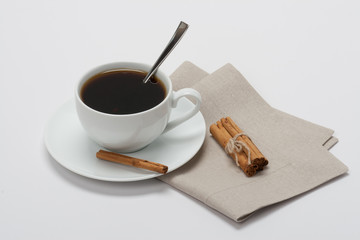 Black Coffee In White Cup And Cinnamon Sticks On Folded Natural