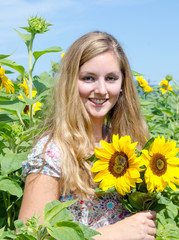 Happiness: Young pretty woman relaxing in sunflower field :)