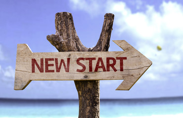 New Start wooden sign with a beach on background