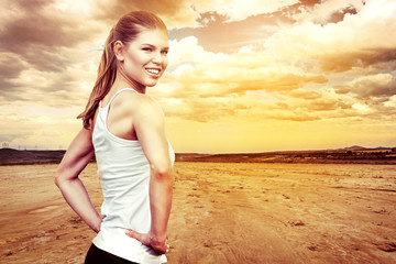 Happy smiling female runner stretching body at the beach