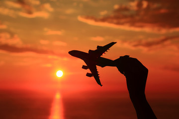Silhouette of hand holding airplane miniature