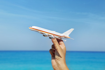 Hand holding airplane miniature with blue horizon background
