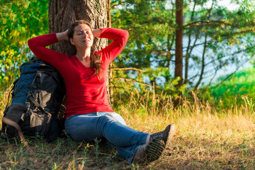 strongly weary backpacker resting against a tree