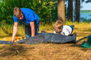 child with his father to install a tent
