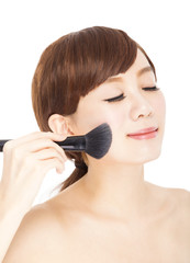 closeup of  young woman using brushes makeup her face