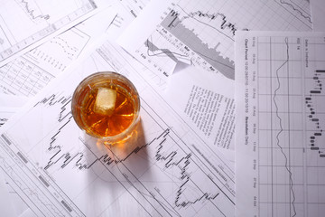 Glass of whiskey on charts