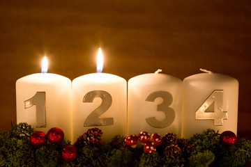 Advent Candles in a row on a gold colored background.