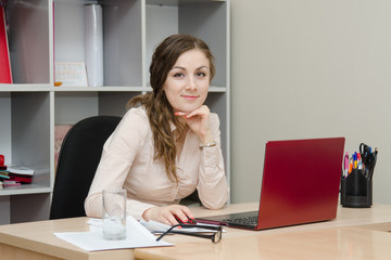 Portrait of girl at a laptop in the office
