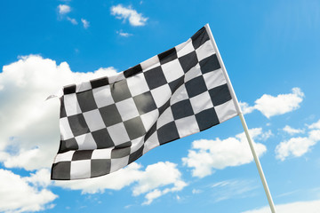 Checkered flag waving in the wind with clouds on background
