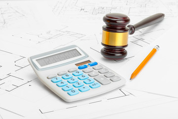Gavel with calculator and pencil over construction blueprint
