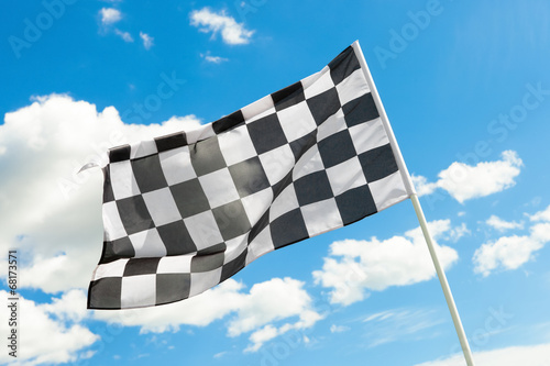 Fotobehang Formule 1 Checkered flag waving in the wind with clouds on background