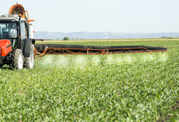 Farmer in red tractor spraying soybean field