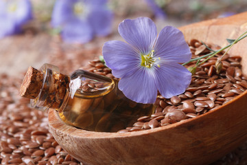 flax oil in a glass bottle, flowers and seeds in a spoon macro