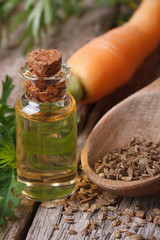 essential oil of carrot seeds in a bottle on a table  vertical