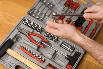 Hands holding ratchet and head over toolbox