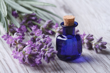 lavender oil in a glass bottle on a background flowers