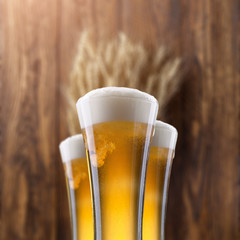 Glass of beer with wheat on wood