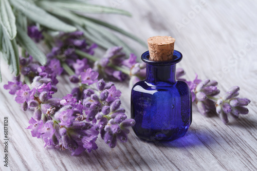 Deurstickers Lavendel lavender oil in a glass bottle on a background flowers