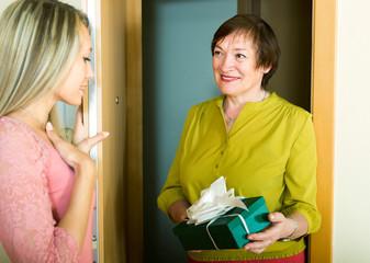 elderly woman congratulating young girl