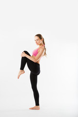 Young beautiful sports girl does fitness exercise