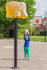 Young girl aiming ball at basket like elephant