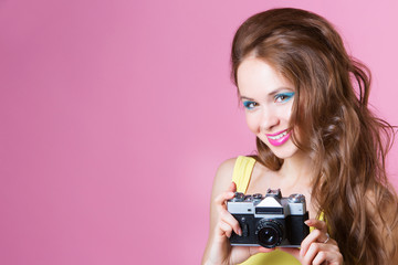 Young beautiful woman on pink background holding a camera