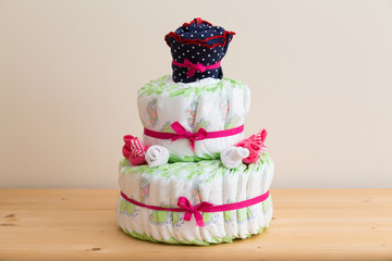 Fake layered cake made from diapers, babysocks, and a babydress