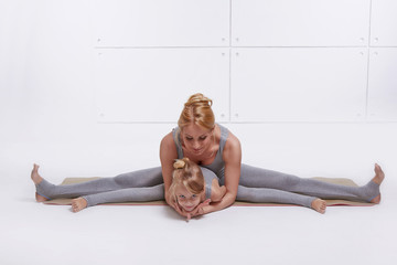 Mother daughter doing yoga exercise, fitness, gym sports paired