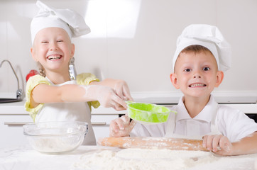 Cheeky happy little boy and girl in the kitchen