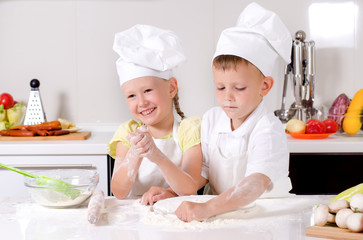 Happy little boy and girl cooking in the kitchen