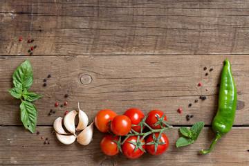 Tomatoes, basil, mint, garlic and pepper on dark wood