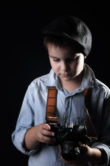 Boy with old camera. Dark background. Retro style.