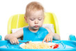 Little blond boy eating spaghetti with fork