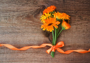 Bouquet from flowers of calendula with orange satin ribbon on wo