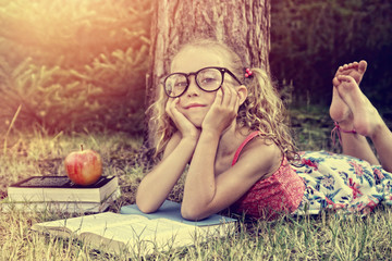Girl reading a book on a glade - vintage style