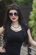 Elegant woman wearing black dress and sunglasses