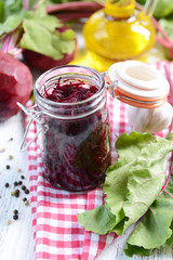 Grated beetroots in jar on table close-up