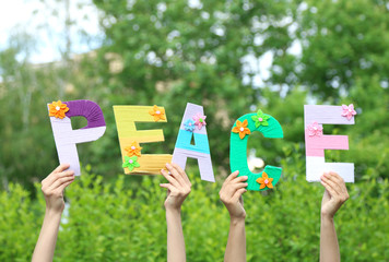 Hands holding up letters building word peace
