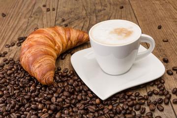 Tasse Cappuccino mit Croissant und Kaffeebohnen