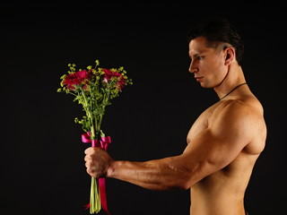 Muscular man holds bouquet of gerberas on the dark background