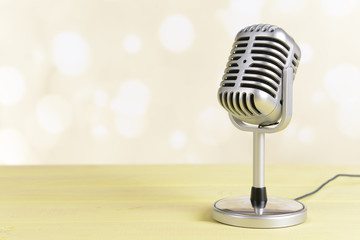 Vintage microphone on table on light yellow background