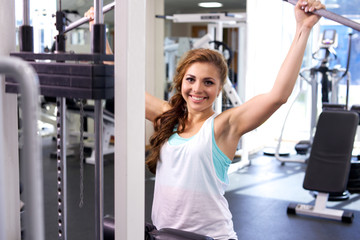 Young Woman Uses Lat Machine