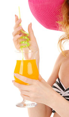 Beautiful young woman in swimsuit and hat with cocktail