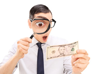 Excited man looking at dollar bill with magnifier