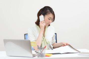 電話しながら書類を見る女性